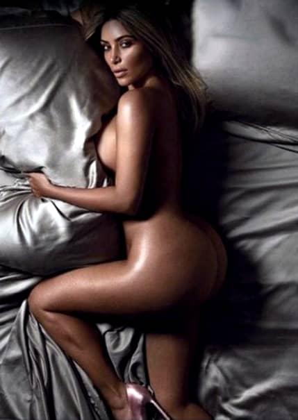 Kim Kardashian goala în pat, pe așternuturi de culoare gri