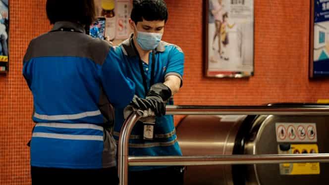 Fotografia macabră care captează pericolul epidemiei cu coronavirus din China. Un cadavru este păzit de oameni în costum. FOTO