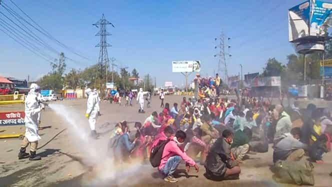 Imagini revoltătoare! Zeci de muncitori dezinfectați cu substanțe toxice în mijlocul străzii, în India