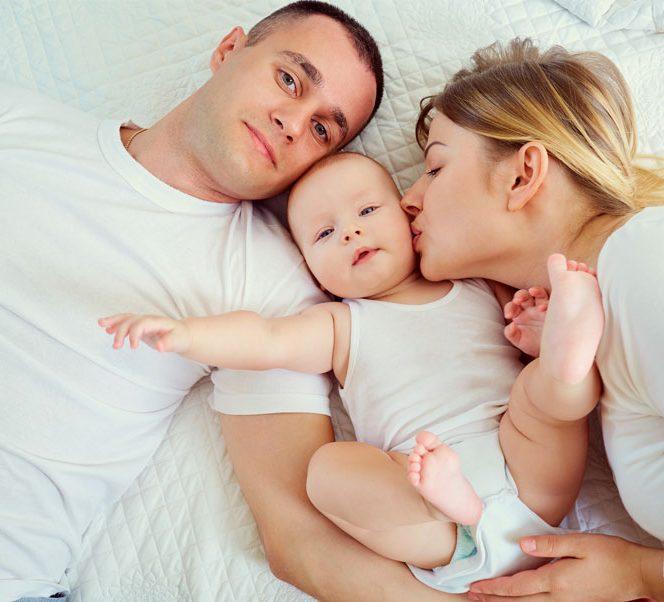 mama si tata in pat alaturi de bebelus