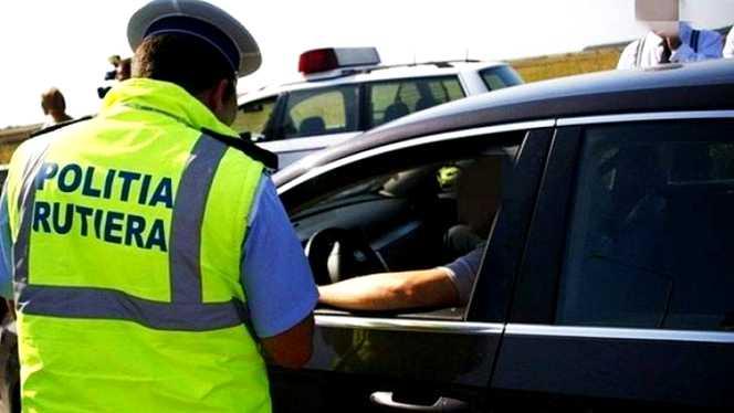 Noi modificări au fost aduse Codului Rutier! În imagine, un poliţist de la Rutieră în timp ce disuctă cu un şofer tras pe dreapta la marginea drumului