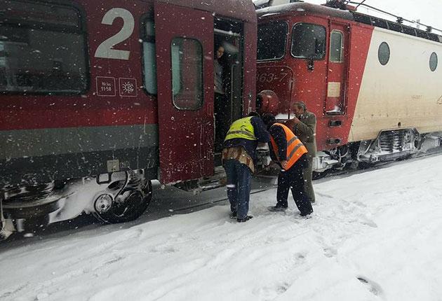 Doi angajaţi ai CFR deszăpezesc un tren în gară
