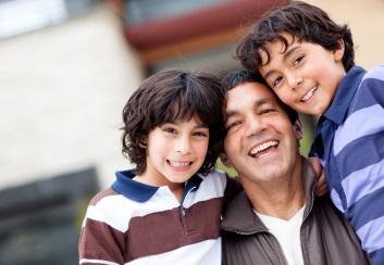 Aşa arată o familie monoparentală, compusă dintr-un părinte bărbat şi cei doi copii. fotografie cu o familie zâmbitoare