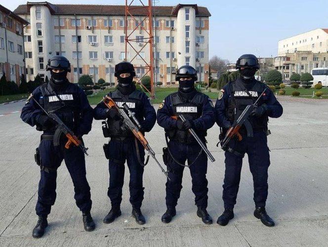 Patru reprezentanţi ai Jandarmeriei Române, fotografiaţi cu armele la piept