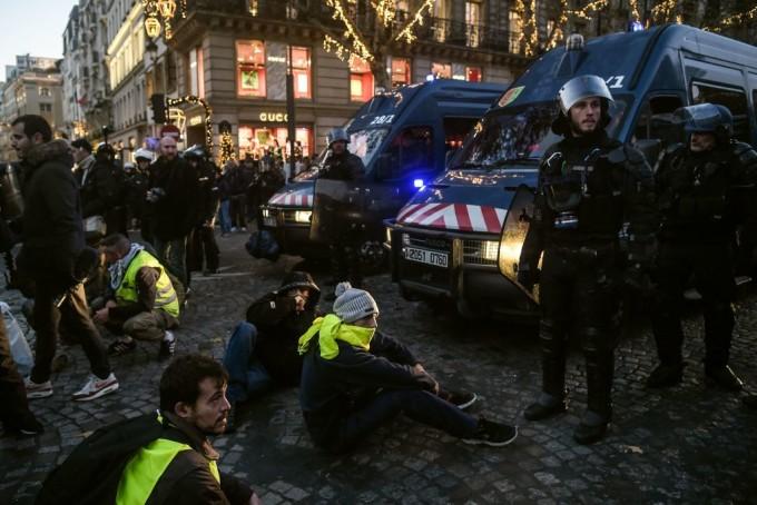 Protestatarii se aşează pe jos în timp ce protestează pentru preţurile crescute ale carburanţilor. Din imagine se vede cum mai mulţi protestatari stau întinşi pe jos pe străzile franţuzeşti
