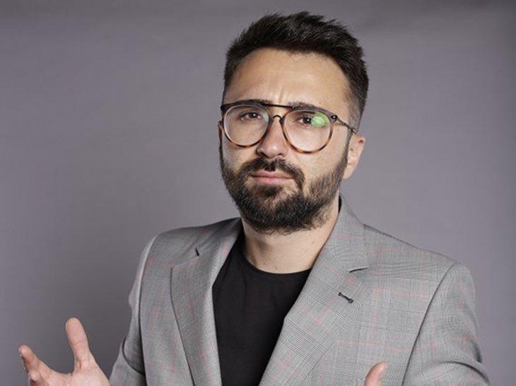 Ionuţ Cristache, prezentatorul de la TVR cu un salariu uriaş, în timpul unei şedinţe foto de promovare a emisiunii sale. Acesta gesticulează