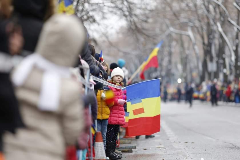 Imagine de la parada militară care are loc de 1 decembrie, cu ocazia Zilei Naţionale a României. O fată flutură drapelul