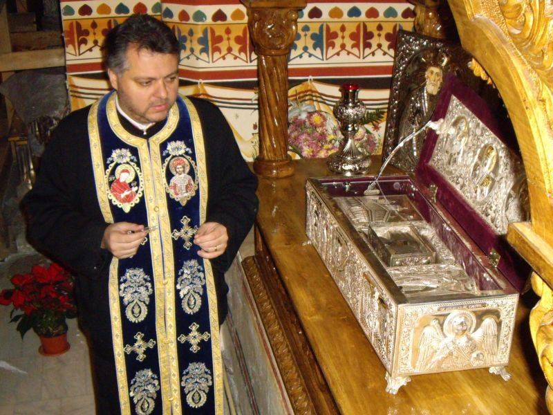 Preotul Emil Nedelea Cărămizaru lângă racla cu mâna Sfântului Nicolae, aflată la biserica Sfântul Gheorghe Nou din București, chiar la kilometrul zero al României