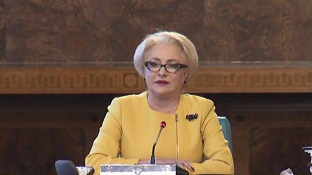 Premierul României, Viorica Dăncilă, în timpul unui discurs. Prim-ministrul poartă ochelari negri şi sacou galben