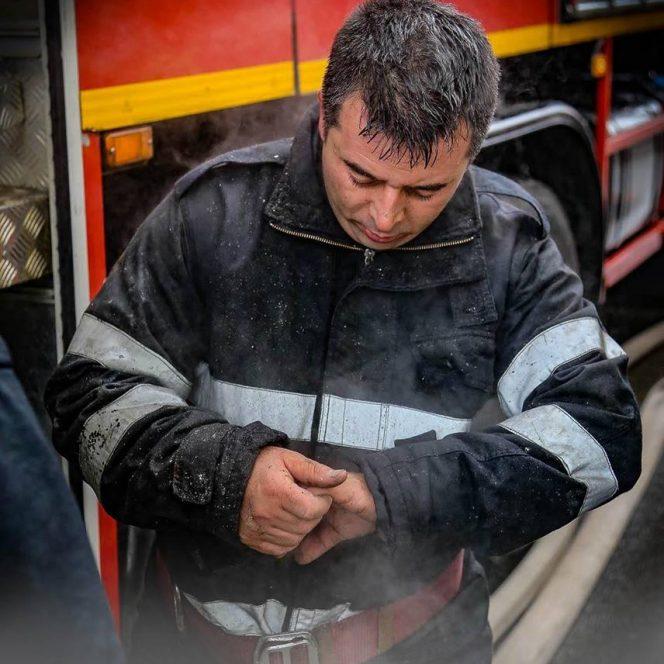 Imaginea pompierului cu uniforma udă, stând în ger, după intervenție.