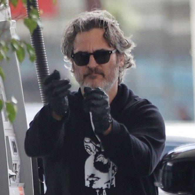 Joaquin Phoenix poartă mănuși la benzinărie